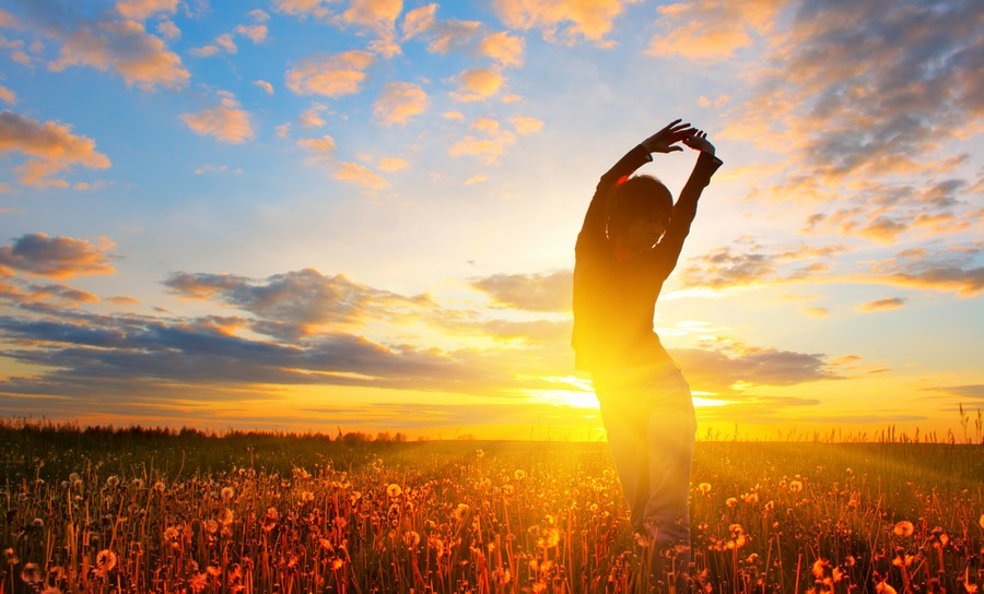 Person-stretching-in-field-under-sun_web