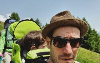 man with sungalsses and baby carrier hiking in the Dolomites